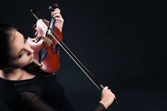 Beautiful young woman playing violin over black Stock Photos