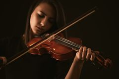Beautiful young woman playing a violin over black background Stock Images