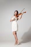 Beautiful young woman playing violing. Portrait of beautiful young woman in white dress playing violin.Studio shot stock photos