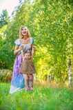 Beautiful young woman plays child field Stock Images