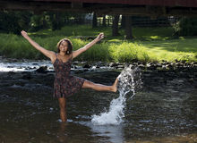 Beautiful young woman plays in creek Stock Photography