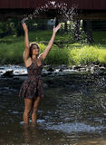 Beautiful young woman plays in creek Stock Photo