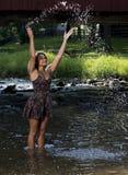 Beautiful young woman plays in creek Stock Photo