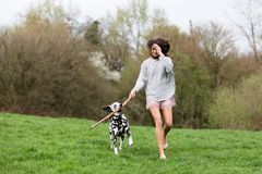 Young woman plays with an Dalmatian dog outdoors. Beautiful young woman plays with an Dalmatian dog outdoors Royalty Free Stock Images
