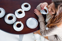 Beautiful young woman with plenty of coffee cups Royalty Free Stock Image
