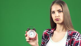 Beautiful young woman pointing at the alarm clock looking serious. Studio close up of a beautiful young serious woman looking at the alarm checking time pointing stock image