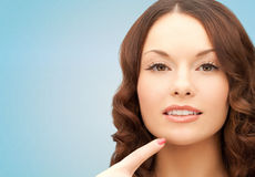 Beautiful young woman pointing finger to her chin Stock Photography