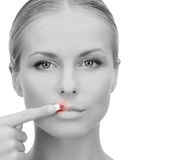 Beautiful young woman pointing finger to her lips. Medicine, beauty, people and health concept - beautiful young woman pointing finger to her lips over white Stock Photo