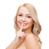 Beautiful young woman pointing finger to lips Royalty Free Stock Photo