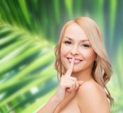 Beautiful young woman pointing finger to lips. Health and beauty concept - clean face of beautiful young woman pointing finger to her lips Royalty Free Stock Image