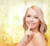 Beautiful young woman pointing finger to lips Royalty Free Stock Photography
