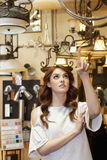 Beautiful young woman pointing finger up in lights store Stock Images