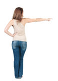 Beautiful young woman  pointing at wall. Rear view. Royalty Free Stock Photography
