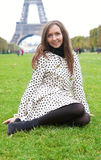 Beautiful young woman in polka dot trench near. Beautiful young woman in polka dot trench sitting on grass near the Eiffel Tower royalty free stock images