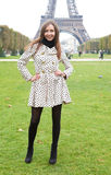 Beautiful young woman in polka dot trench in Paris. Beautiful young woman in polka dot trench near the Eiffel Tower royalty free stock photo