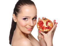 Beautiful young woman with a pomegranate. Stock Photos