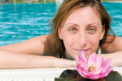 Beautiful young woman at pool with lotus flower Royalty Free Stock Photos