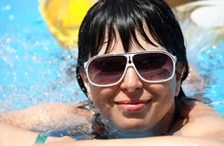 Beautiful young woman at a pool, in sunglasses Stock Image