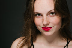 Beautiful young woman portrait on black background studio with red lips and freckles Royalty Free Stock Images