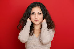 Beautiful young woman portrait with black long curled hair on red Royalty Free Stock Photography