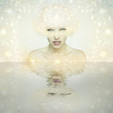 Brightness. Beautiful young woman portrait with brightness headdress like a goddess with her reflection on the water royalty free stock photography