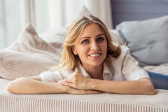 Beautiful young woman. Portrait of beautiful young woman in casual clothes looking at camera and smiling, lying on sofa at home Royalty Free Stock Photography
