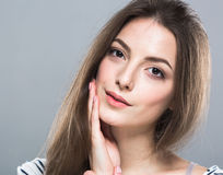 Beautiful young woman portrait cute tender pure smiling touching her cheek by palm attractive gray background Stock Photos