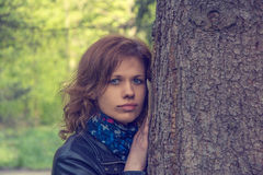 Beautiful young  woman. Portrait of beautiful young dreaming woman standing near a tree Stock Photography