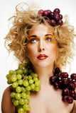 Beautiful young woman portrait excited smile with fantasy art ha. Ir makeup style, fashion girl with creative food fruit orange, grapes, citrus make up, happy Royalty Free Stock Image