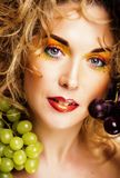Beautiful young woman portrait excited smile with fantasy art ha. Ir makeup style, fashion girl with creative food fruit orange, grapes, citrus make up, happy Stock Photography