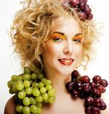 Beautiful young woman portrait excited smile with fantasy art ha. Ir makeup style, fashion girl with creative food fruit orange, grapes, citrus make up, happy Stock Image