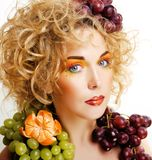 Beautiful young woman portrait excited smile with fantasy art ha. Ir makeup style, fashion girl with creative food fruit orange, grapes, citrus make up, happy Stock Photos