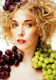 Beautiful young woman portrait excited smile with fantasy art ha. Ir makeup style, fashion girl with creative food fruit orange, grapes, citrus make up, happy Royalty Free Stock Photo