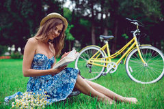 Beautiful young woman portrait reading a book with bicycle in the park. stock photography