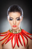 Beautiful young woman portrait with red hot and spicy peppers Stock Photo