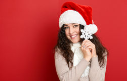 Beautiful young woman portrait in santa helper hat with big snowflake posing on red Royalty Free Stock Photo