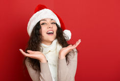 Beautiful young woman portrait in santa helper hat posing on red Stock Photography