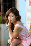 Beautiful young woman posing alone at the outdoor cafe. Model is Thai Ethnicity Stock Photos