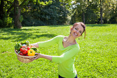 Beautiful young woman posing with basket full of vegetables Royalty Free Stock Image