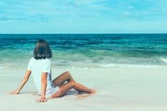 Beautiful young woman posing on the beach of a tropical island of Bali, Indonesia. Beautiful young woman in sunglasses posing on the beach of a tropical island Royalty Free Stock Photo