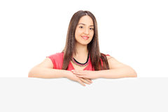 Beautiful young woman posing behind a blank signboard. Isolated on white background Stock Images