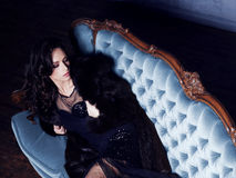 Beautiful and young woman posing in black dress on blue sofa. Vi Stock Image