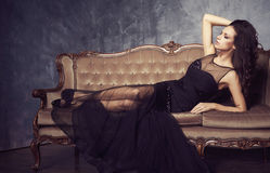 Beautiful and young woman posing in black dress on brown sofa. V. Intage interior and retro background Royalty Free Stock Image