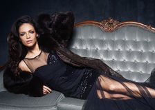 Beautiful and young woman posing in black dress on grey sofa. Vi Royalty Free Stock Images
