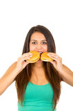 Beautiful young woman posing for camera holding two hamburgers next to mouth, smiling happily, white studio background.  Stock Photography