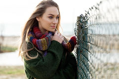 Beautiful young woman posing in a cold winter on the beach. Royalty Free Stock Photo