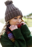 Beautiful young woman posing in a cold winter on the beach. Stock Photos