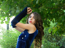 Beautiful young woman,posing in deep blue dress. Royalty Free Stock Image