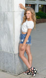 Beautiful young woman posing in denim shorts and white top Royalty Free Stock Images