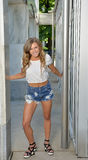 Beautiful young woman posing in denim shorts and white top Stock Photo